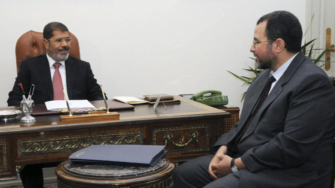 FILE - In this Sunday, July 22, 2012 file photo released by the Egyptian Presidency, Egyptian President, Mohammed Morsi, left, meets with the minister of Water Resources and Irrigation, Hesham Kandil, at the Presidential Palace in Cairo. Egypt's Islamist president is to swear in a new Cabinet as tensions rise over the country's tenuous security, recent sectarian violence and popular discontent over issues such as widespread water and power outages. The U.S.-educated Kandil will announce the Cabinet lineup on Thursday before he and his ministers are sworn in by Morsi. (AP Photo/Ahmed Mourad, Egyptian Presidency, File)