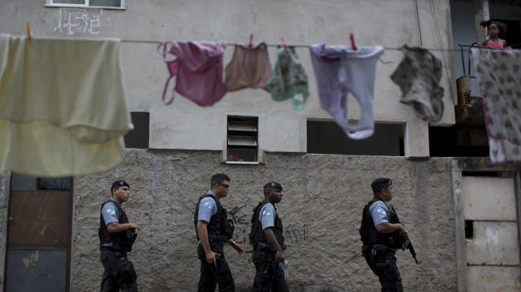 Policemen from the Pacifying Police Unit, or 'UPP', patrol in the Varginha area of the Manguinhos slum complex where Pope Francis will visit next week during his trip to Rio de Janeiro, Brazil, Sunday, July 21, 2013. In one of the key events of his trip, the church's first Jesuit leader will venture into this rough slum that sits along a violence-soaked road known by locals as the Gaza Strip. (AP Photo/Felipe Dana)
