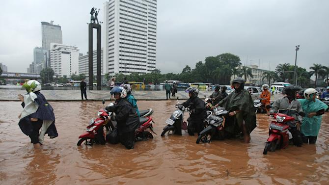 Indonesians push their motorcycles through a flooded street in Jakarta, Indonesia, Thursday, Jan. 17, 2013. Flooding caused by monsoon rains have forced thousands of people to flee their homes in Indonesia's capital. (AP Photo/Achmad Ibrahim)