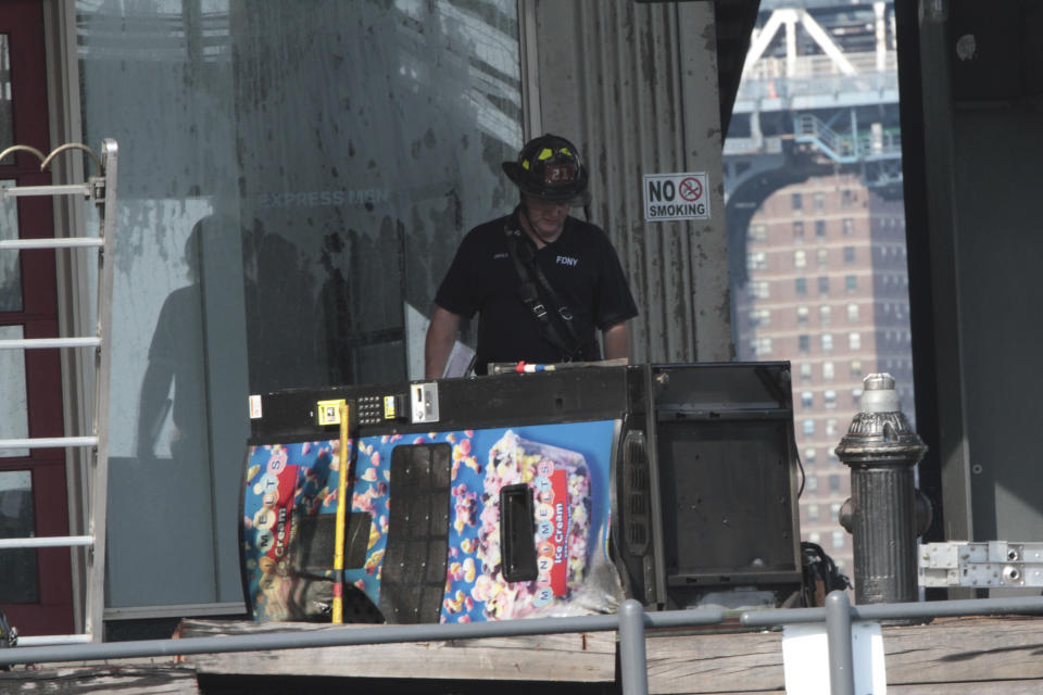 A firefighter looks at a vending machine on Pier 17 in New York on Saturday, July 14, 2012 after a three-alarm fire at the South Street Seaport. Fire officials said there were no injuries. (AP Photo/Mary Altaffer)