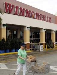 FILE - In this Dec. 1, 2004 file photo, a shopper leaves a Winn-Dixie store in Miami. The supermarket chain Winn-Dixie is being sold for $560 million to Bi-Lo LLC. (AP Photo/David Adame, File)