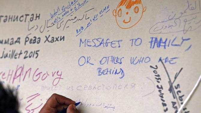 An asylum seeker scribbles on a message board at a makeshift help centre after crossing the border into the European Union's visa-free Schengen travel zone, in Szeged