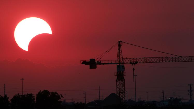 The moon begins to partially block the sun as the sun sets at 8:02 p.m. silhouetting a crane just west of downtown Houston during a rare solar eclipse known as the