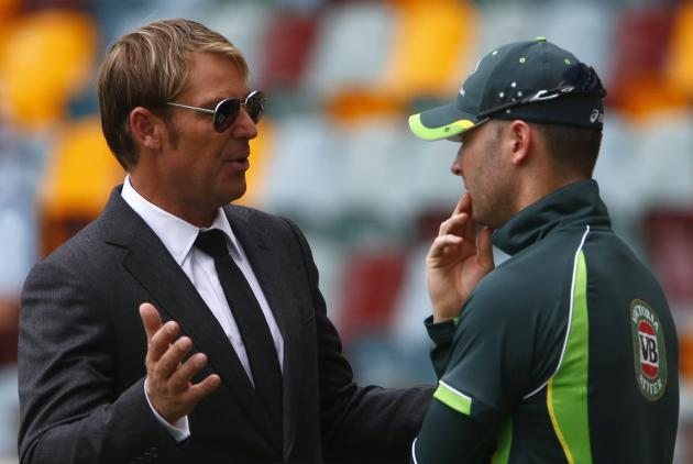 Australia's former cricketer Warne discusses with captain Clarke before the start of the third day's play of the first Ashes cricket test match against England in Brisbane