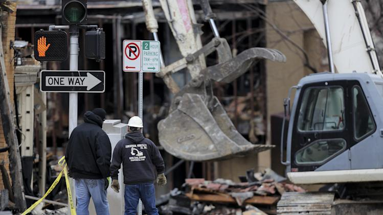 Two men look at the rubble of JJ's restaurant after an explosion and fire tore through the establishment Tuesday evening near the Country Club Plaza Wednesday, Feb. 20, 2013, in Kansas City, Mo. The fire killed one person and injuring over a dozen. (AP Photo/Ed Zurga)