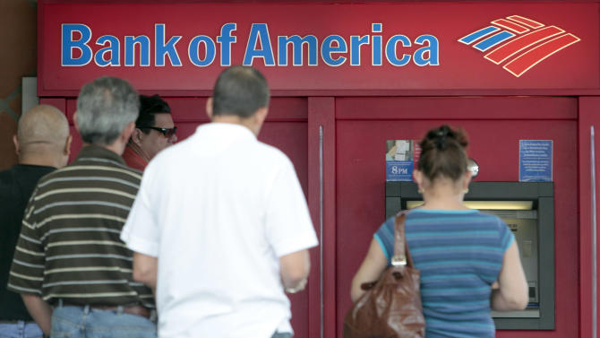 FILE - This Friday, Oct. 14, 2011 file photo shows customers in line a Bank of America ATM in Hialeah, Fla. Banks begin to report their results in mid-January from the last three months of 2011. JPMorgan Chase will be the first major bank to report results Friday, Jan. 13, 2012 followed by Citigroup, Wells Fargo, Goldman Sachs, Bank of America and Morgan Stanley.  (AP Photo/Alan Diaz, File)