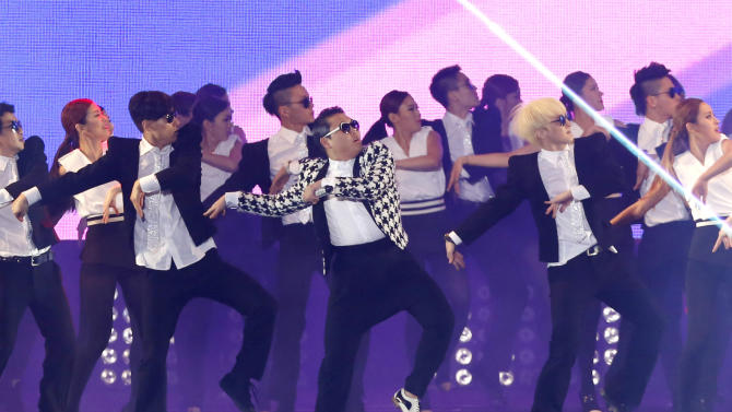 """FILE - In this Saturday, April 13, 2013 file photo, South Korean rapper PSY, in a checkered jacket, performs his new song """"Gentleman"""" in his concert titled """"Happening"""" in Seoul, South Korea. A major South Korean broadcaster says it has banned PSY's new music video because the rapper is shown abusing public property. The """"Gentleman"""" video opens with PSY kicking a cone that says """"no parking."""" (AP Photo/Kin Cheung)"""