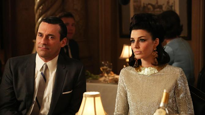 """This TV publicity image released by AMC shows Jon Hamm as Don Draper, left, and Jessica Pare as Megan Draper in a scene from """"Mad Men."""" AMC is keeping """"Mad Men"""" around an extra year, expanding the final season of this acclaimed drama series to 14 episodes and portioning them equally in 2014 and 2015. The network said Tuesday, Sept. 17, 2013, that seven episodes will air next spring and another seven in 2015. (AP Photo/AMC, Michael Yarish, File)"""