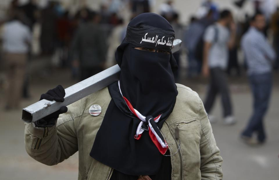 "In this Monday, April 30, 2012 photo, an Egyptian women wearing the Niqab with Arabic writing that reads, ""down with military rule,"" carries a metal pole as a weapon at the road leading to the Ministry of Defense, in Cairo, Egypt. (AP Photo/Fredrik Persson)"
