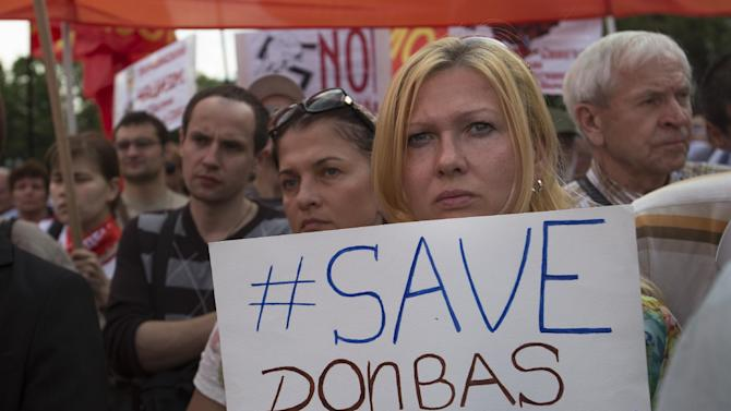 "A woman holds a poster reading ""Save Donbas People"" as Russian Communists party activists gather in support of pro-Russian fighters and local citizens who live in Donetsk and Luhansk regions of eastern Ukraine in Moscow, Russia, Thursday, July 3, 2014. Ukraine's president shook up the leadership of his struggling military on Thursday, appointing a new defense minister and top general tasked with stamping out the corruption that has left the country's armed forces faltering before a pro-Russian insurgency. (AP Photo/Alexander Zemlianichenko)"