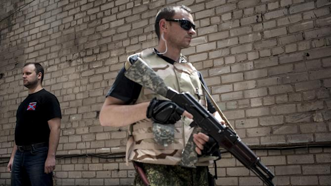 Pavel Gubarev, self-proclaimed people's governor, left, and a pro-Russian fighter stand in Donetsk, eastern Ukraine, Tuesday, June 10, 2014. Ukraine's new president on Tuesday ordered security officials to create a corridor for safe passage for civilians in eastern regions rocked by a pro-Russian insurgency, as he began to form his government team by tapping a media mogul as chief of staff. (AP Photo/Evgeniy Maloletka)