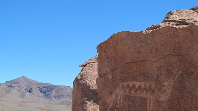 This August 2012 photo shows a petroglyph of a two-headed creature in Yerbas Buenas, San Pedro de Atacama in Chile. Thousands of petroglyphs decorate these rocks. (AP Photo/Karen Schwartz)