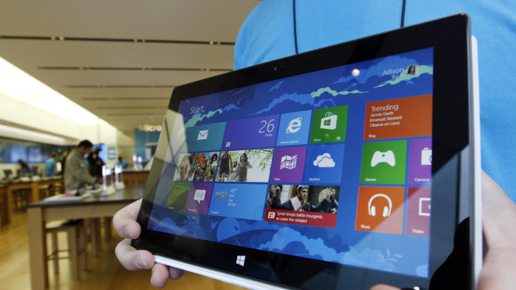 A Microsoft store product advisor displays the new Surface table computer as customers enter the store as it opens Friday, Oct. 26, 2012 in Seattle. Friday was the first day of sales for the new Windows 8 operating system and the company's new tablet computer, the Surface. (AP Photo/Elaine Thompson)