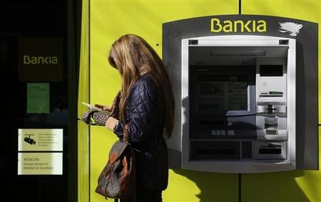A woman stands beside an ATM at a branch of Spanish lender Bankia in Madrid February 15, 2013. REUTERS/Sergio Perez