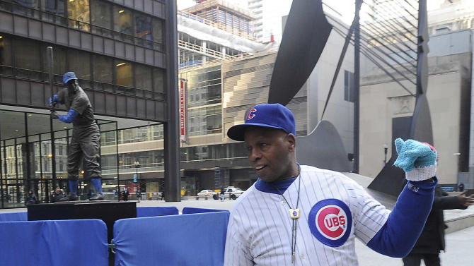 Chicago Cub's super fan Ronnie Wickers walks by a statue of Cubs Hall of Famer ErnieBanks that was placed in Daley Plaza, as baseball fans get their first chance to pay their respects, Wednesday, Jan. 28, 2015, in Chicago. The city and the Cubs took the unprecedented step of taking the statue out of storage, where it was being held while the ballpark is renovated, and put it on public display away from its usual home at Wrigley Field. Banks died on Friday, Jan. 23, 2015. He was 83. (AP Photo/Daily Herald, Mark Welsh )  MANDATORY CREDIT, MAGS OUT