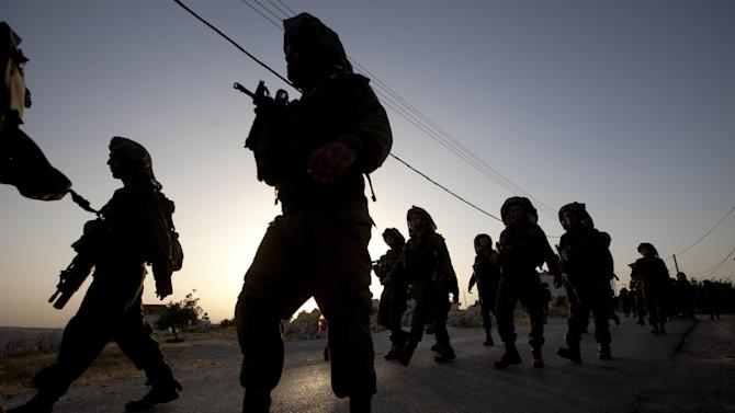 Israeli soldiers patrol during a military operation to search for three missing teenagers outside the West Bank city of Hebron, Monday, June 16, 2014. Israeli security forces searched the West Bank, looking for three missing teenagers, including an American, who they fear have been abducted by Palestinian militants. (AP Photo/Majdi Mohammed)