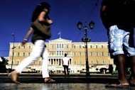 People walk by the Greek parliament in Athens. The Greek conservative and socialist parties have suffered massive losses in an election marked by anti-austerity anger, with a leftist party opposing EU-IMF reforms making gains, exit polls showed