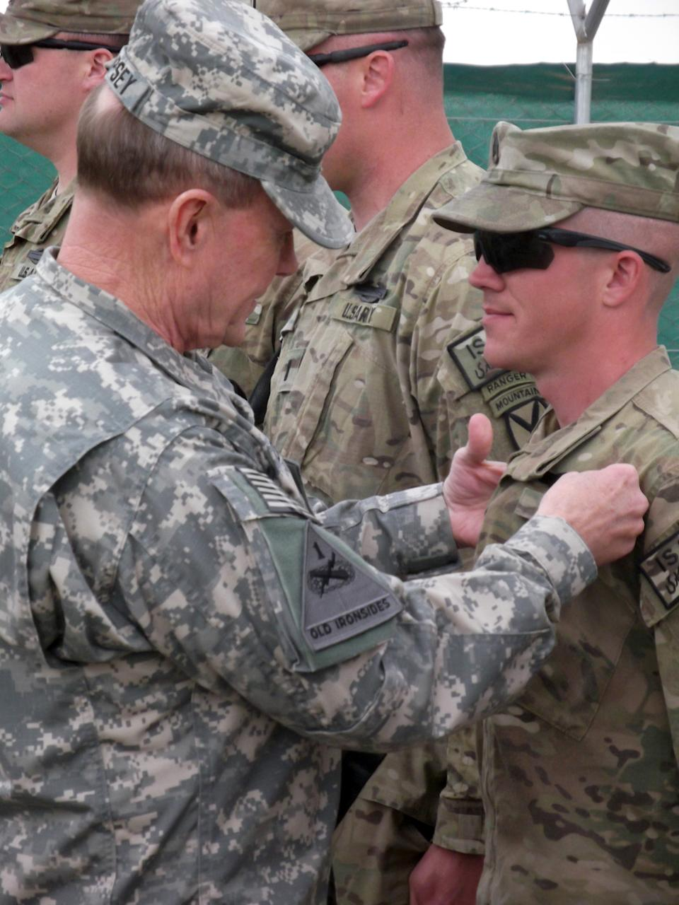 U.S. Chairman of the Joint Chiefs of Staff, Gen. Martin Dempsey, pins a Combat Infantrymen Badge on an unidentified soldier at Forward Operating Base Sharana in Afghanistan's Paktika province during his visit to the base Sunday, April 7, 2013. (AP Photo/Robert Burns)