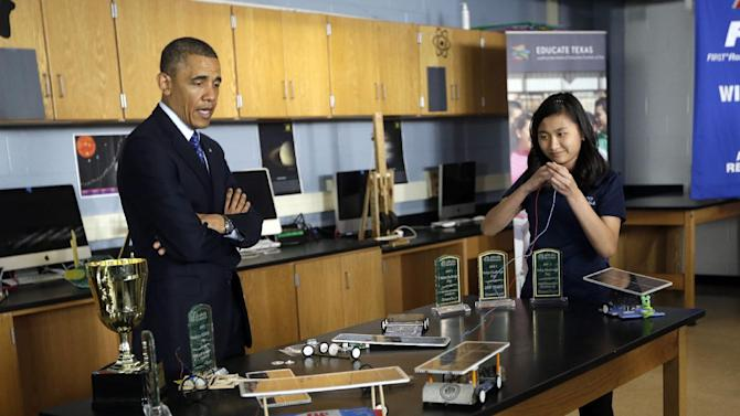 President Barack Obama, left, watches student Anh Ly, right, control a solar powered vehicle during a classroom visit to Manor New Technology High School, Thursday, May 9, 2013 in Manor, Texas. (AP Photo/Pablo Martinez Monsivais)