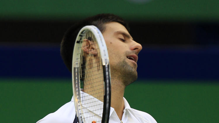 Novak Djokovic of Serbia reacts after missing a return shot against Feliciano Lopez of Spain during their third round match of the Shanghai Masters tennis tournament at Qizhong Forest Sports City Tennis Center in Shanghai, China, Thursday Oct. 11, 2012. Djokovic won 6-3, 6-3. (AP Photo/Eugene Hoshiko)