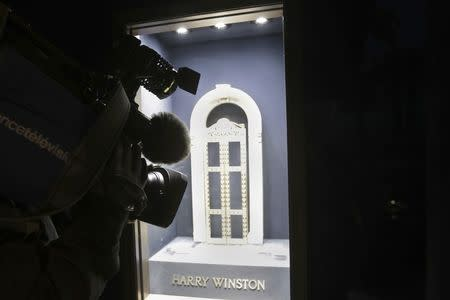 A television cameraman makes images of an empty display window at luxury jewellers Harry Winston after a robber stole diamonds worth 15 million euros ($16 million) in Cannes