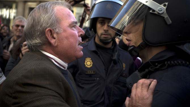 A demonstrator argues with a riot police officer during a general strike in Madrid, Spain, Wednesday, Nov. 14, 2012. Spain's General Workers' Union said the nationwide stoppage, the second this year, was being observed by nearly all workers in the automobile, energy, shipbuilding and constructions industries. (AP Photo/Daniel Ochoa de Olza)