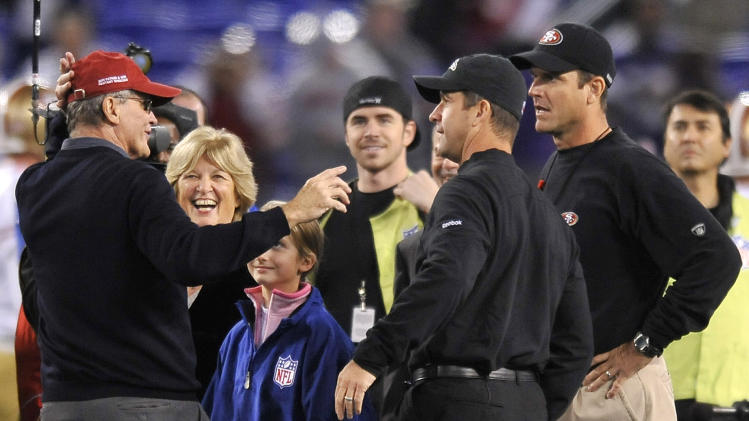 FILE - In this Nov. 24, 2011 file photo, Jack Harbaugh, far left, and his wife Jackie, second from left, chat with sons Baltimore Ravens head coach John Harbaugh, second from right, and San Francisco 49ers head coach Jim Harbaugh before an NFL football game in Baltimore. The entire Harbaugh family already got its Super Bowl victory last Sunday, when each coach did his part to ensure a family reunion in New Orleans next week. The Ravens face off against the 49ers in the first Super Bowl coached by siblings on opposite sidelines. (AP Photo/Gail Burton, File)