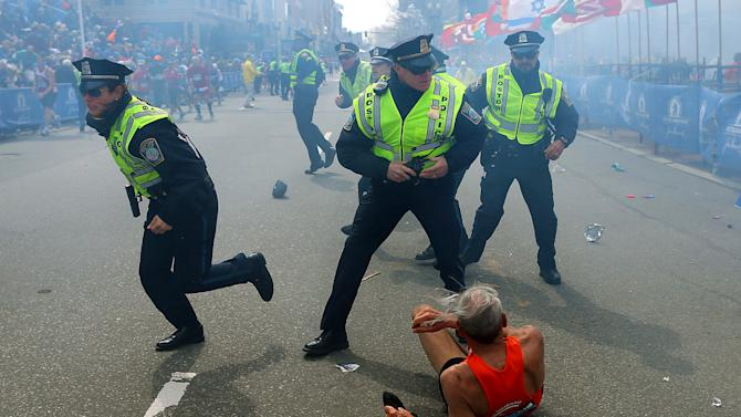 FILE - In this Monday, April 15, 2013 file photo, Bill Iffrig, 78, lies on the ground as police officers react to a second explosion at the finish line of the Boston Marathon in Boston. Iffrig, of Lake Stevens, Wash., was running his third Boston Marathon and near the finish line when he was knocked down by one of the two bomb blasts. Since Monday, Boston has experienced five days of fear, beginning with the marathon bombing attack, an intense manhunt and much uncertainty ending in the death of one suspect and the capture of the other. (AP Photo/The Boston Globe, John Tlumacki, File) MANDATORY CREDIT: THE BOSTON GLOBE, JOHN TLUMACKI