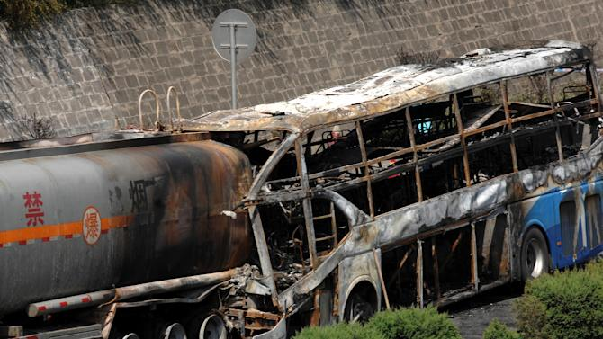 In this photo released by China's Xinhua News Agency, the burnt wreckage of a double-decker sleeper bus and a tanker loaded with highly-flammable methanol sit on a highway in Yan'an City, northwest China's Shaanxi province on Sunday, Aug. 26, 2012. The 39-seat bus rammed into the tanker early Sunday, causing both vehicles to burst into flames and killing 36 people, state media said. (AP Photo/Xinhua, Li Yibo) NO SALES