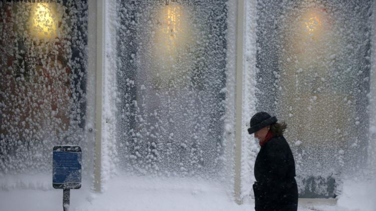 A woman walks past windows covered with snow at the Seaport World Trade Center in Boston early Saturday, Feb. 9, 2013. (AP Photo/Gene J. Puskar)