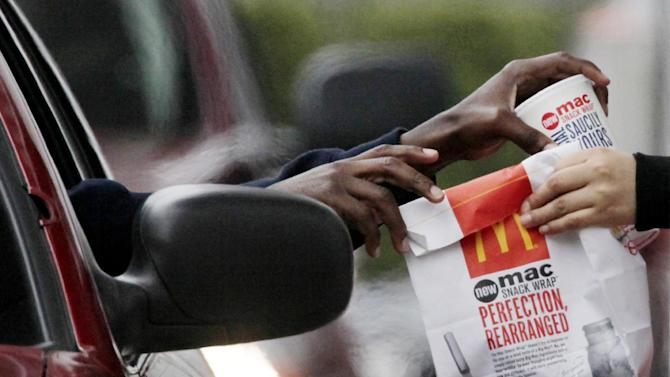 FILE - In this Jan. 22, 2010 file photo, a customer grabs lunch at a McDonalds drive-through in Chicago. Fast-food chains such as McDonald's, Burger King and Wendy's are trumpeting pricier, premium offerings to shed their image as purveyors of greasy junk food and convince customers to spend a few extra bucks. .(AP Photo/M. Spencer Green, File)