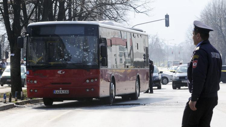 Police officers stand near a damaged city bus after an explosion in Banja Luka