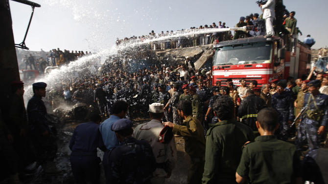 Firefighters work to extinguish a fire at the wreckage of a plane after it crashed in Sanaa, Yemen, Wednesday, Nov. 21, 2012. Yemeni security officials say a military plane has crashed during training over the capital, Sanaa, killing all 10 people on board. (AP Photo/Hani Mohammed)