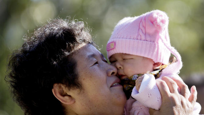 A Chinese woman plays with her grandchild at the Ritan Park in Beijing Wednesday, Oct. 31, 2012. A government think tank says China should start phasing out its one-child policy immediately and allow two children for every family by 2015. It remains unclear whether Chinese leaders are ready to take that step. (AP Photo/Andy Wong)