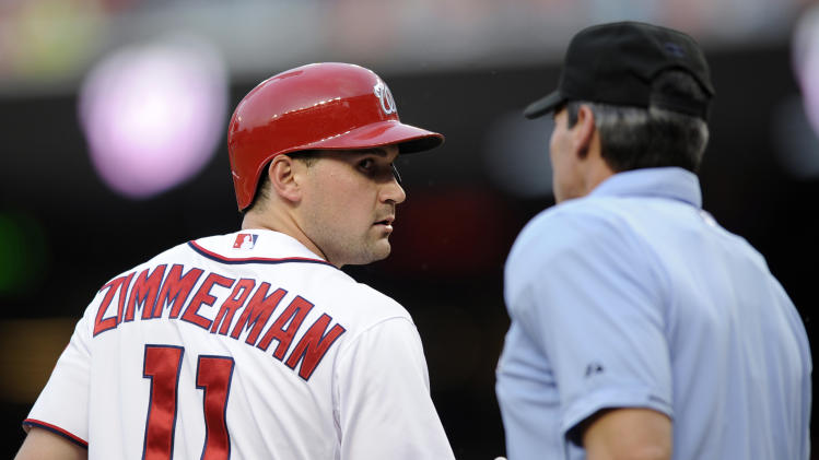 Washington Nationals' Ryan Zimmerman (11) looks at home plate umpire Angel Hernandez, right, as he heads to the dugout after he was called out on strikes against the Chicago Cubs during the first inning of a baseball game, Friday, May 10, 2013, in Washington. (AP Photo/Nick Wass)