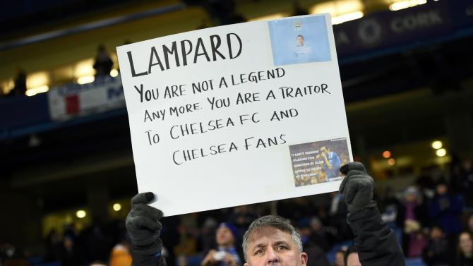 A Chelsea supporter holds up a placard before the start of their English Premier League soccer match against Manchester City at Stamford Bridge in London