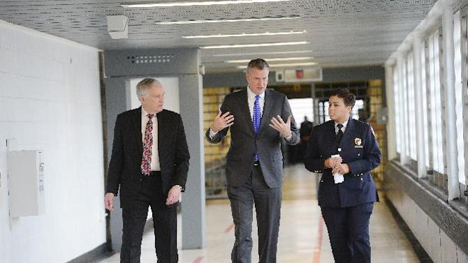 New York City Mayor Bill de Blasio is joined by, from left, Department Correction Commissioner Joe Ponte and Warden Becky Scott during his tour of Second Chance Housing at Rikers Island jail facility on Wednesday, Dec. 17, 2014 in New York.  The facility serves as alternative housing for incarcerated adolescents.  De Blasio  announced the city has ended its longstanding practice of sending 16- and 17-year-old inmates to solitary confinement for breaking rules.  (AP Photo/The Daily News, Susan Watts, Pool)