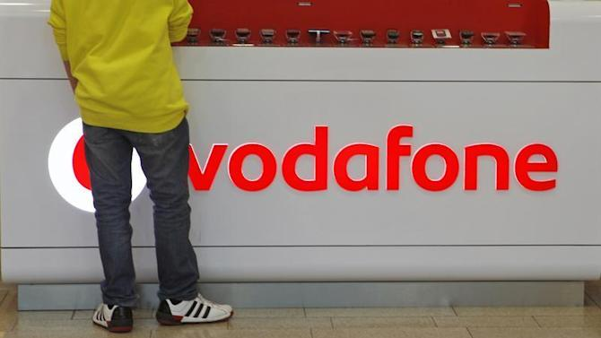 A customer stands next to the Vodafone logo in a shopping mall in Prague