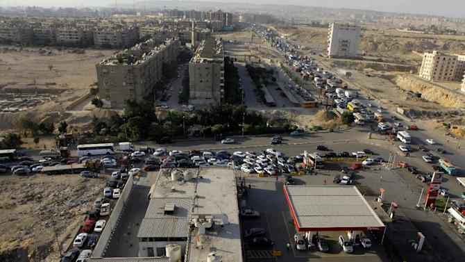 General view showing a traffic jam surround a gasoline station as drivers wait in long queues in Cairo, Egypt, Tuesday, June 25, 2013. Fuel shortages have caused long lines for months, but Egypt's Supply Minister Bassem Ouda told a news conference that the latest fuel shortage will end in a matter of days. Authorities blame the shortage on a technicalproblem at a majorpetrol depoton the outskirts of Cairo. (AP Photo/Amr Nabil)