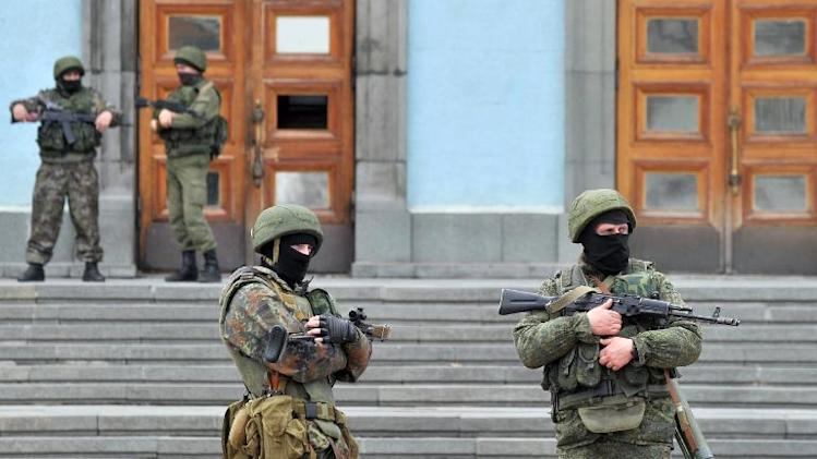 Unidentified armed and uniformed men guard the Crimean Cabinet of Ministers building in Simferopol on March 2, 2014