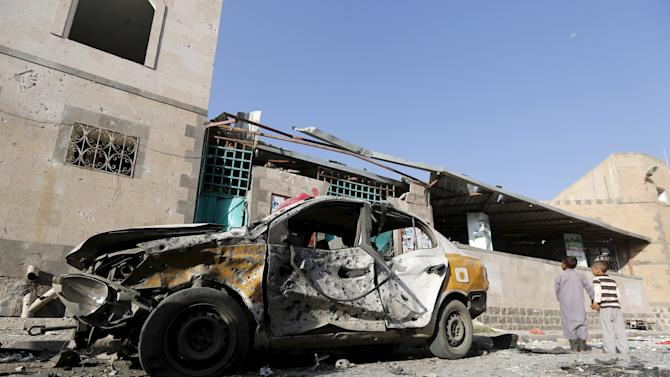 Boys stand outside a mosque hit by two bombings in Yemen's capital Sanaa