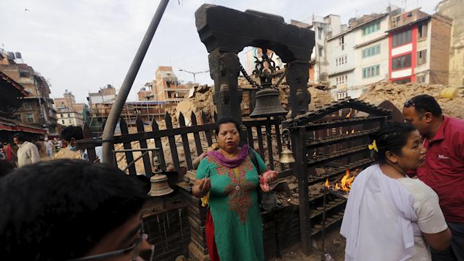 A woman prays in front of a destroyed temple at Bashantapur Durbar Square, after the earthquake in Kathmandu