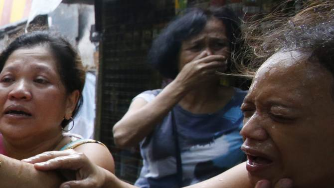 Residents of a squatter colony react to tear gas fired by policemen, during a demolition of shanties at the colony to pave way for private modern housing projects in Mandaluyong