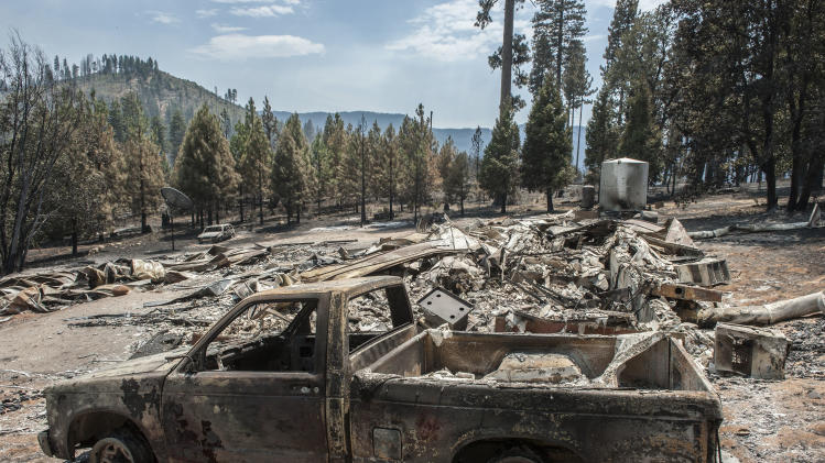 A burned home and pickup truck lie in the Foresta community in Yosemite National Park in California on Tuesday, July 29, 2014. Fire crews gained ground Tuesday on two of the largest wildfires in California, lifting evacuation orders for about half the homes in the path of a blaze in Yosemite National Park and redeploying firefighters battling another fire in the Sierra Nevada foothills east of Sacramento. (AP Photo/Al Golub)