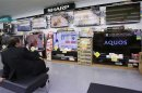 File photo of a man looking at Sharp Corp's Aquos television sets displayed at an electronics store in Tokyo