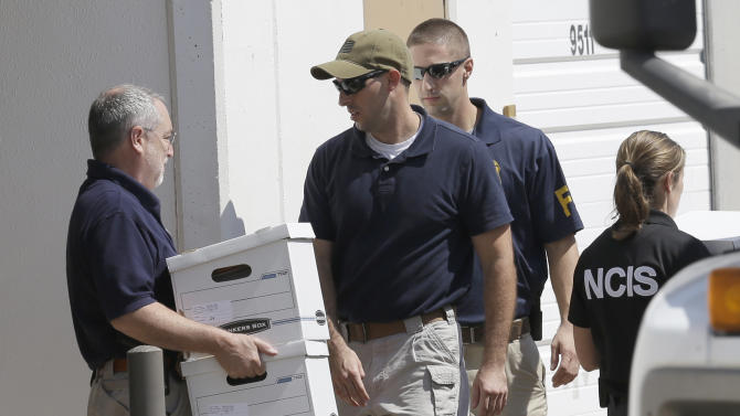 Federal agents carry boxes out of Arc Electronics Inc. Wednesday, Oct. 3, 2012 in Houston. A Kazakhstan-born businessman was charged in the U.S. on Wednesday with being a secret Russian agent involved in a scheme to illegally export microelectronics from the United States to Russian military and intelligence agencies. (AP Photo/David J. Phillip)