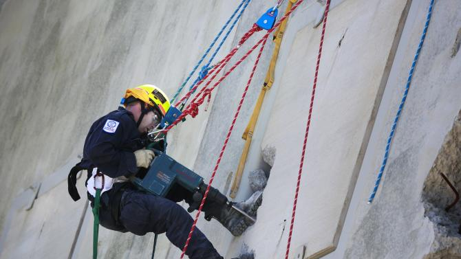 A rescue specialists for USA-1 repels while using a jackhammer to rescue a victim from the scene of a mock disaster area during a training exercise at the Guardian Center in Perry