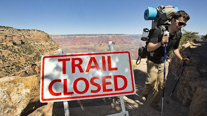Grand Canyon Park Closed-10-1-2013- Sebastian Ramirez, 27, of Austin, Texas, hikes out of the Bright Angel Trail in Grand Canyon National Park, Tuesday afternoon. Ramirez spent the night with friends in the bottom of the Canyon at Bright Angel Campground. Beginning at 6 am, visitors were told the park was closed and they could not visit. (AP Photo/The Arizona Republic, Tom Tingle) MARICOPA COUNTY OUT; MAGS OUT; NO SALES MBO