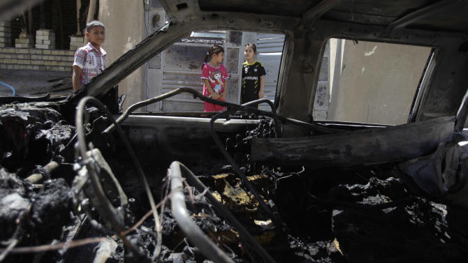 Civilians inspect the aftermath of a car bomb attack in Baghdad, Iraq, Wednesday, July 24, 2013. A bomb exploded near a Sunni mosque in Baghdad's southern Dora neighborhood on Tuesday, killing four and wounding 12, police said. (AP Photo/Karim Kadim)