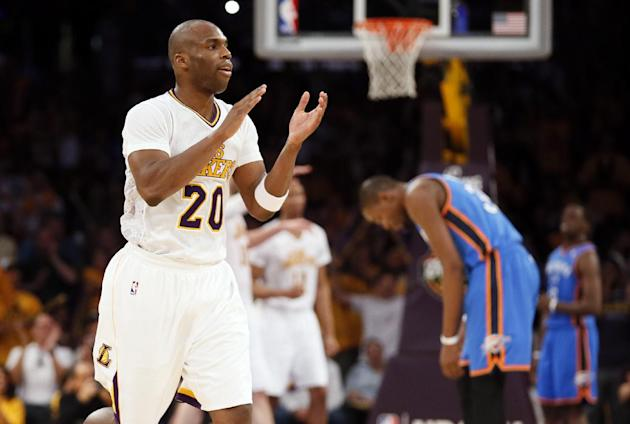 Los Angeles Lakers shooting guard Jodie Meeks, left, celebrates late in the fourth quarter as Oklahoma City Thunder forward Kevin Durant, right, is near during an NBA basketball game in Los Angeles, S